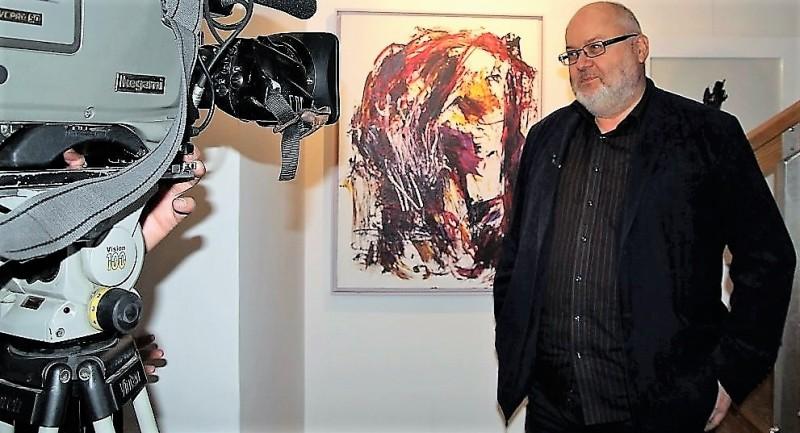 Lechosław Lameński w galerii sztuki spa spot w Nałęczowie. W tle obrazy Jacka Sempolińskiego.