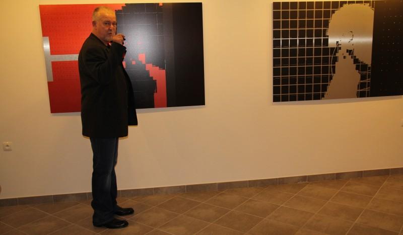 Mirosław Pawłowski na tle swoich grafik w galerii spa spot w Nałęczowie.